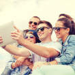 Group of smiling teenagers looking at tablet pc — Stock Photo #46084953