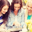 Three beautiful girls looking at tablet pc in cafe — Stock Photo #46601363
