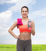 Sporty woman with towel and water bottle — Stock Photo