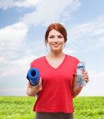 Smiling girl with bottle of water after exercising — Stock Photo