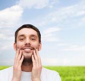Beautiful smiling man touching his face — Foto Stock