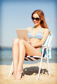 Girl looking at tablet pc on the beach — Stock Photo