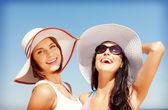 Holky v kloboucích na pláži — Stock fotografie