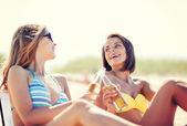 Flickor med drinkar på strandstolar — Stockfoto