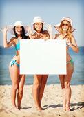 Flickor med tomt ombord på stranden — Stockfoto