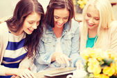 Three beautiful girls looking at tablet pc in cafe — Stock Photo