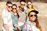 Dospívající dívka s sluchátka a přátelé venku — Stock fotografie