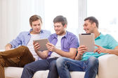 Smiling friends with tablet pc computers at home — Stock Photo