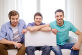 Smiling male friends holding white blank board — Stock Photo