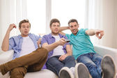 Smiling friends with remote control at home — Stock Photo