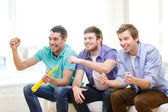Happy male friends with vuvuzela watching sports — Stock Photo