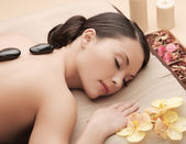 Asian woman in spa with hot stones — Stock Photo