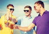 Group of male friends having fun on the beach — Stock Photo