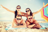 Group of smiling people having fun on the beach — Stock Photo