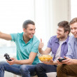 Smiling friends playing video games at home — Stok fotoğraf