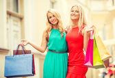 Two beautiful women with shopping bags in the ctiy — Stock Photo