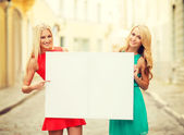 Two happy blonde women with blank white board — Stock Photo