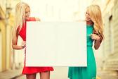 Två glada blonda kvinnor med tom vit tavla — Stockfoto