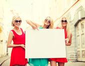Three happy blonde women with blank white board — Stock Photo