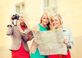 Women with tourist map and camera in the city — Stock Photo