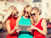 Beautiful girls toursits looking into tablet pc — Stock Photo