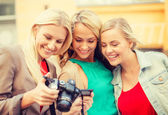Beautiful blonde women with camera in the city — Stock Photo