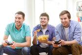 Usmíval se přáteli, kteří hrají videohry doma — Stock fotografie