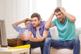 Sad male friends with vuvuzela watching sports — Stock Photo