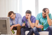 Sad male friends with beer watching sports — Stock Photo