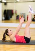 Leende kvinna gör träning på matta i gym — Stockfoto