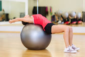 Young woman doing exercise on fitness ball — Stock Photo