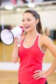 Beautiful sporty woman with megaphone at gym — Stock Photo