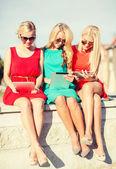 Beautiful girls toursits looking into tablet pcs — Stock Photo