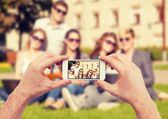 Close up of hands making picture of group of teens — Stock Photo