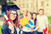 Smiling teenage girl in corner-cap with diploma — Stock Photo