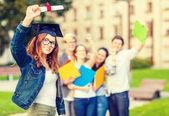 微笑着十几岁的女孩在角帽与文凭 — 图库照片