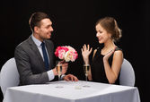 Smiling man giving flower bouquet to woman — Stock Photo