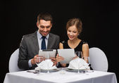 Couple with menus on tablet pc at restaurant — Foto de Stock