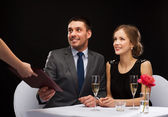 Waiter giving menu to happy couple at restaurant — Stock Photo