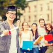 Smiling teenage boy in corner-cap with diploma — Stock Photo #46751917