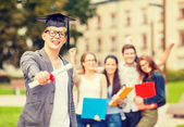 Smiling teenage boy in corner-cap with diploma — Foto de Stock