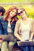 Two female students with laptop computers — Stock Photo