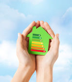 Hands holding green paper house — Stock Photo