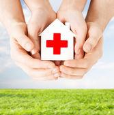 両手赤十字社と紙の家 — ストック写真