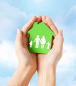 Hands holding green house with family — 图库照片