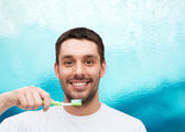 Smiling young man with toothbrush — Stockfoto