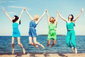 Girls jumping on the beach — Stock Photo