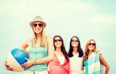 Girl with ball and friends on the beach — Stock Photo