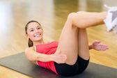 улыбается женщина, делать упражнение на коврике в тренажерном зале — Стоковое фото
