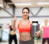 Teenage girl with jar of protein showing thumbs up — Stockfoto